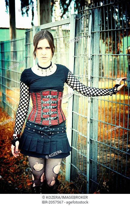 Woman standing next to a fence, Gothic