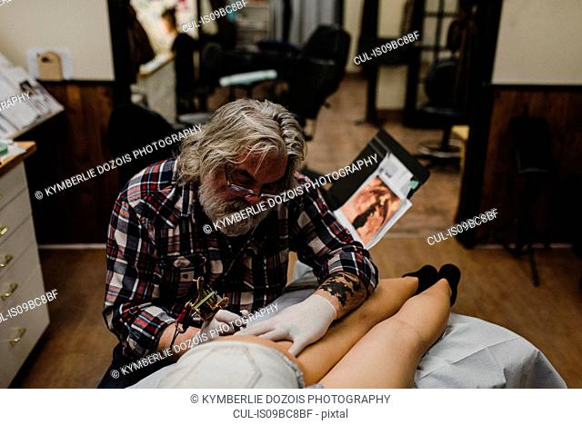 Tattooist tattooing young woman's thigh