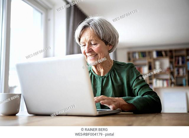 Portrait of senior woman using laptop at home