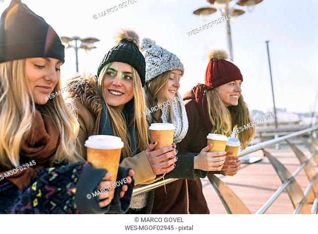 Four friends with coffee to go in winter