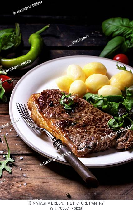 Grilled steak with potatoes and green salad on white ceramic plate over old wooden table