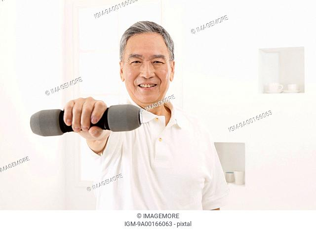 Senior man holding dumbbell and smiling at the camera