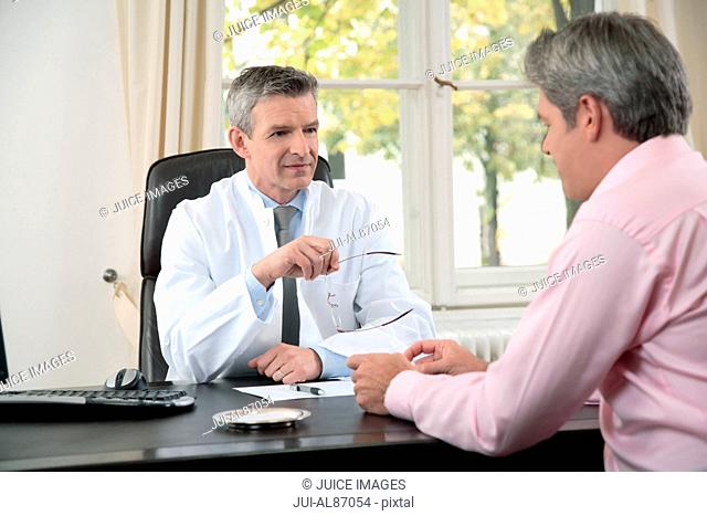Male doctor talking to patient in office