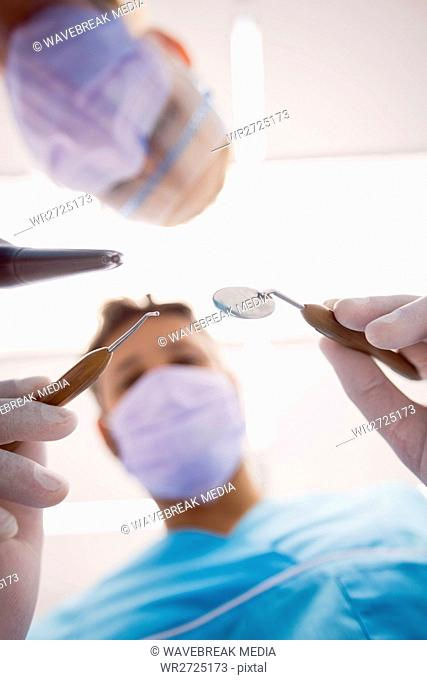 Dentists holding dental tools