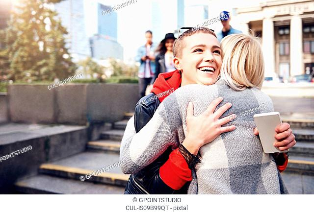 Two young female friends hugging in city