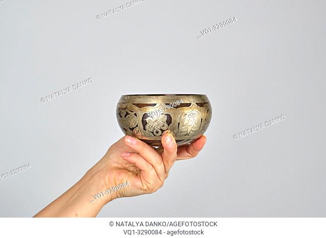 copper singing bowl in female hand on white background