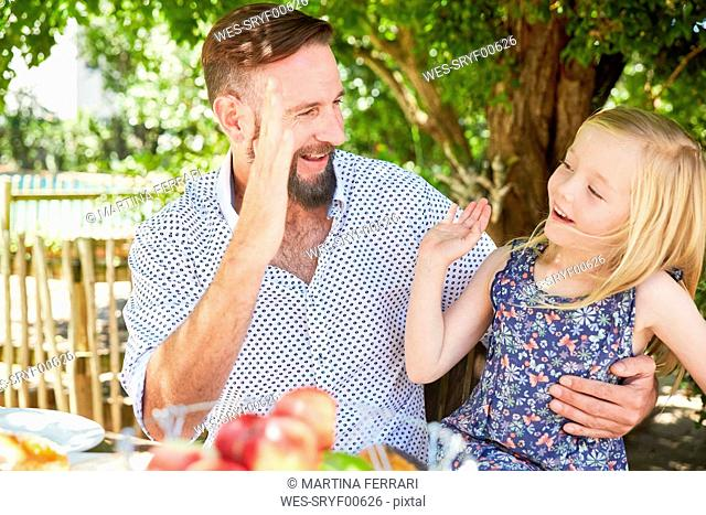 Happy girl with father sitting at garden table high fiving