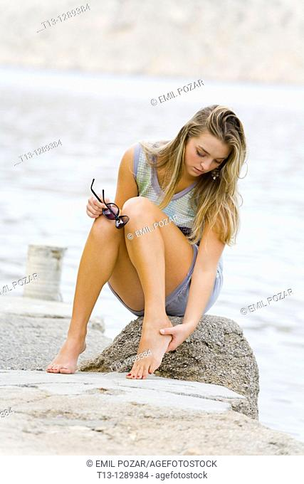 Pain in the foot, young woman on the beach