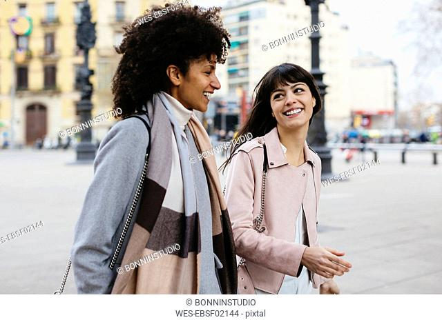 Spain, Barcelona, two happy women walking in the city