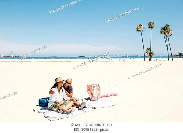 Senior couple sitting on picnic blanket on beach, Long Beach, California, USA