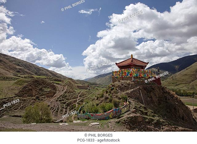 Prayer flags around a small temple. Buddhist shrine. A valley in the mountains