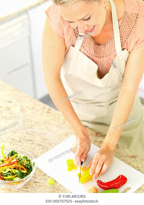 Top view of a happy mature woman cutting vegetables for a salad