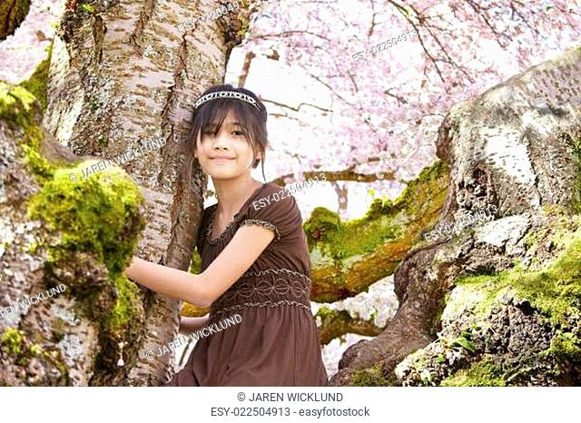 Young girl sitting on branches of flowering cherry tree