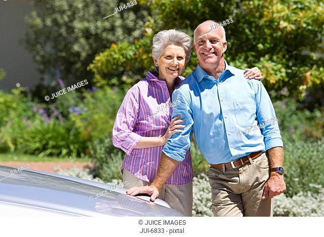 Senior couple standing beside parked car on driveway, woman embracing man, smiling, portrait