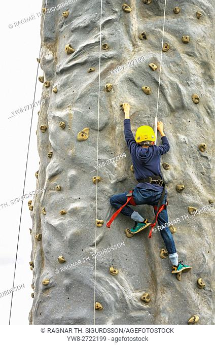 Young boy climbing a wall at The Annual Seaman's Festival, Reykjavik, Iceland
