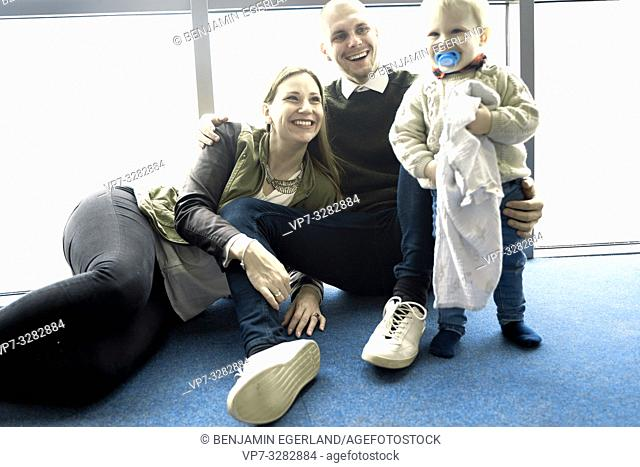 little family, parents with baby toddler child sitting on blue floor at home, in Cottbus, Brandenburg, Germany