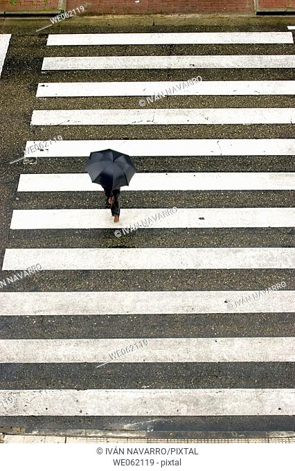 Man with umbrella crossing the street