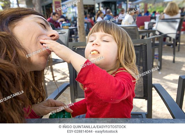 blonde three years old child, with red shirt, feeding woman with cheese puff, sitting in terrace exterior bar cafe with grey chair
