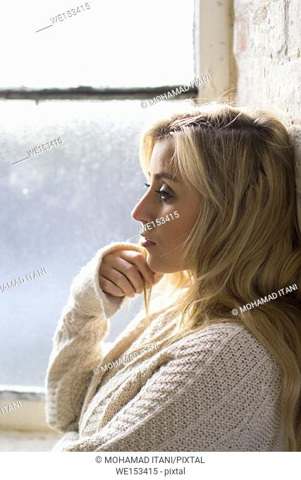 Side view of a sad young blond woman standing by the window looking away