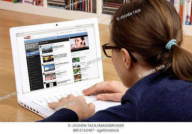 Woman surfing the internet with a laptop, YouTube, movies and video portal, uploading