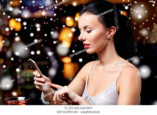 technology, christmas, winter holidays and people concept - young woman texting on smartphone at night club or bar over snow