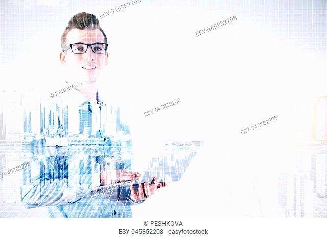 Handsome smiling businessman using laptop on abstract city background with copy space. Double exposure. Communication concept