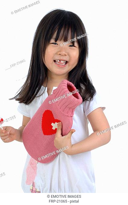 Laughing girl holding lollipop and hot-water bag
