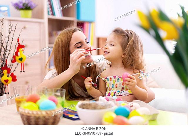 Mother and her baby have fun while painting easter eggs. Debica, Poland