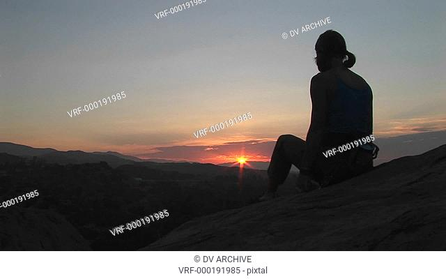 Medium-shot of a woman sitting and stretching with a brilliant golden-hour sky in the background