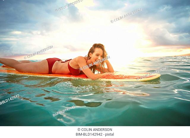 Pacific Islander woman floating on surfboard in ocean
