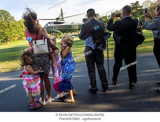The D'Amico family watches as Marine One, carrying United States President Donald Trump, lands on the South Lawn of the White House, in Washington, D