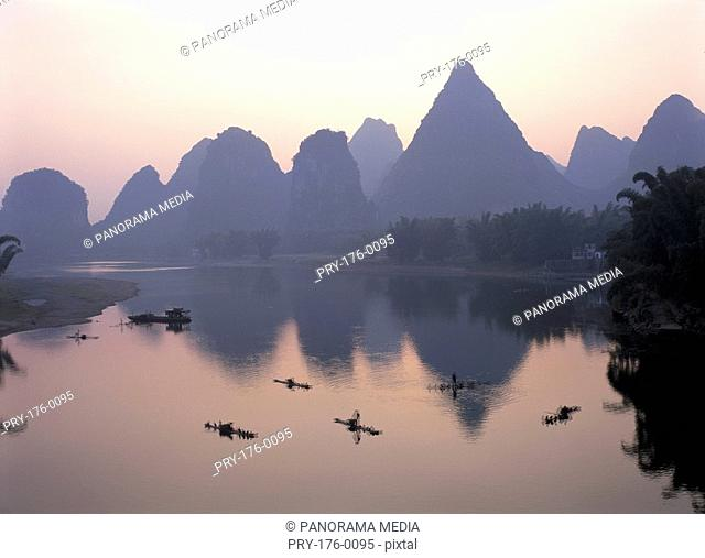 Fishermen on boat and distant mountain-range, Li River, Yangshuo, Guilin