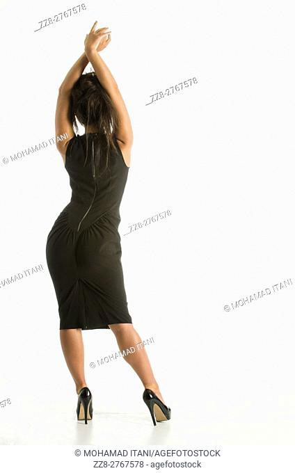Full length of a woman wearing a black dress standing against a white background with hands up