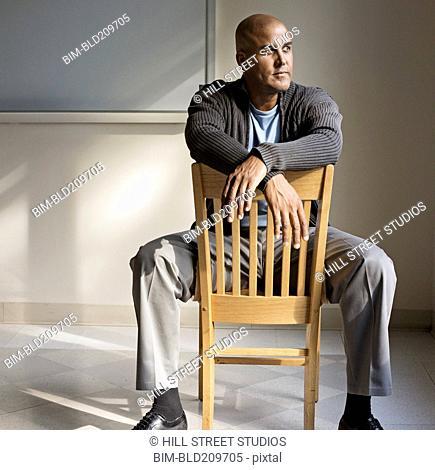Man sitting in wooden chair