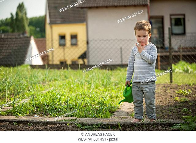 Pensive little boy standing in the garden with children's watering can