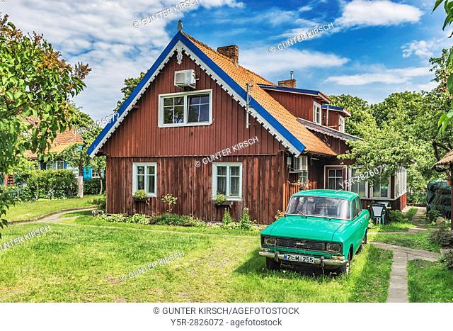 Typical House in Nida. In the garden stands an old car of the brand Moskvitch. Nida (Nidden) is a village on the Curonian Spit to the Baltic Sea