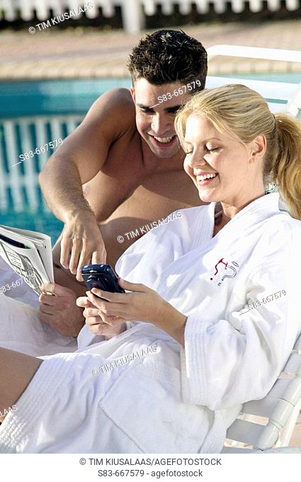 Couple at pool using a blackberry or PDA phone