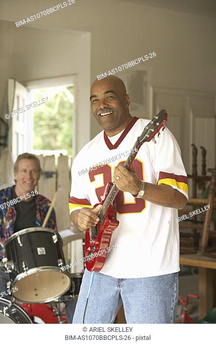 Two middle-aged men playing guitar and drums