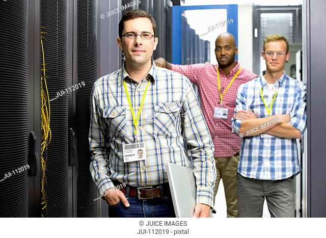 Technicians with laptop looking at camera in data centre server hall