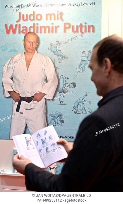 A man leafs through the book 'Judo with Vladimir Putin' at the Leipzig Book Fair in Leipzig, Germany, 23 March 2017. The book explains Judo techniques in 221...
