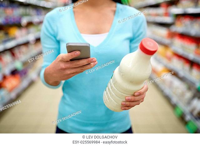sale, shopping, consumerism and people concept - young woman with smartphone holding milk bottle at grocery store or supermarket