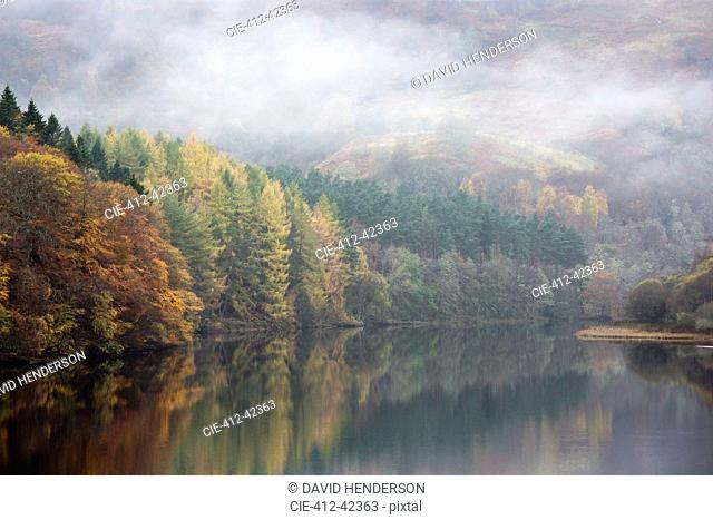 Mysterious fog over tranquil autumn trees and lake, Loch Faskally, Pitlochry, Scotland