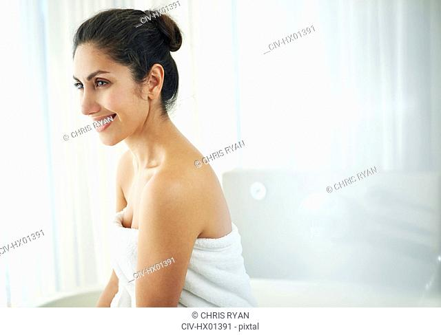 Smiling brunette woman wrapped in towel looking away