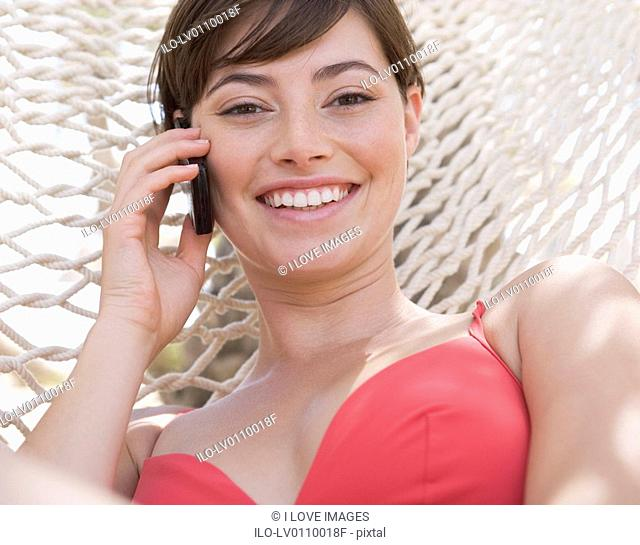 A woman lying in a hammock chatting on a mobile phone