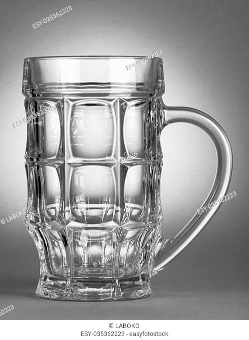 Empty beer glass on grey background and spot light