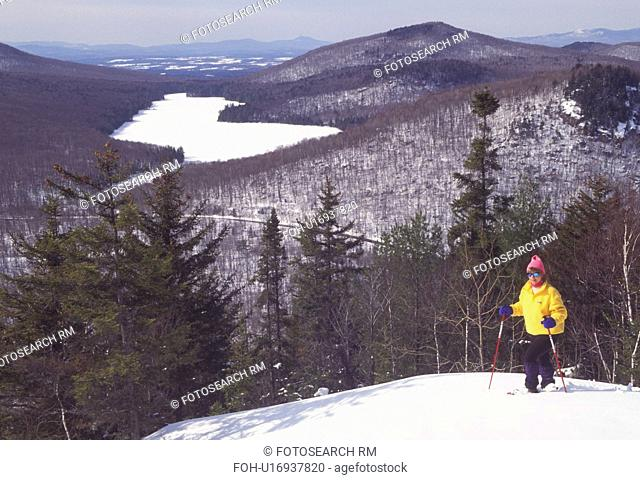 snowshoeing, Vermont, VT, Woman snowshoeing on Owl's Head overlooking the frozen Kettle Pond in Groton State Forest in winter
