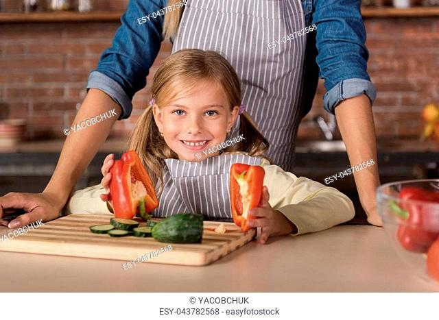 Little cooker. Little smiling merry girl holding a pepper and standing near the table in the kitchen while cooking with her mother