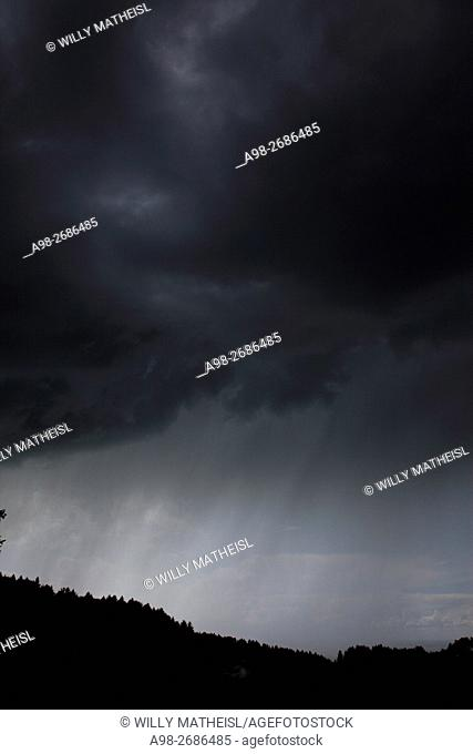Descending dark wall cloud with heavy rainfall above forest, Bavaria, Germany, Europe