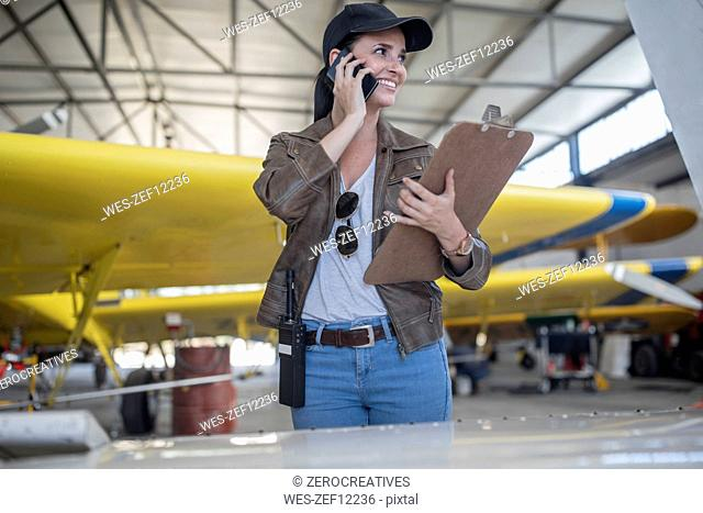 Female pilot talking on the phone in hangar
