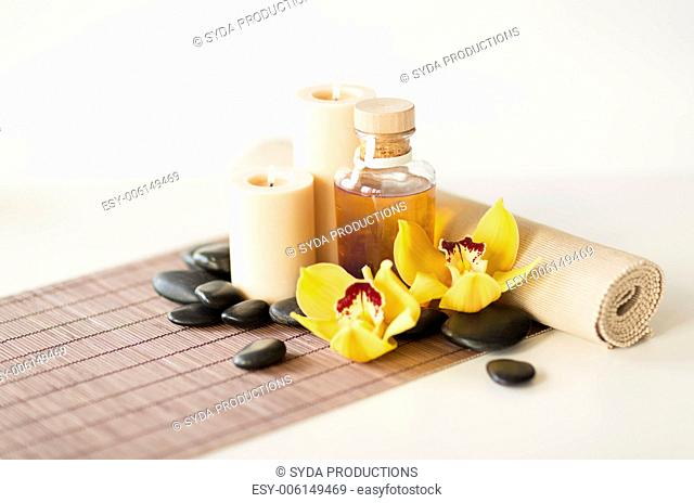 spa, health and beauty concept - closeup of essential oil, massage stones, candles and orchid flower